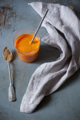 orange carrot smoothie with spoon of brown sugar