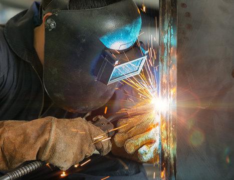 worker welding construction by MIG welding
