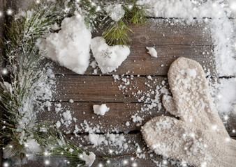white mittens and snow hearts on a wooden background
