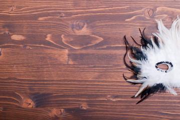 beautiful feather mask on brown board