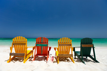 Fototapete - Colorful chairs on Caribbean beach