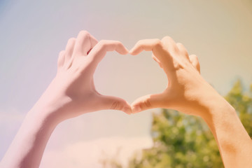 Young woman holding hands in heart shape framing