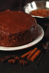 Chocolate cake with chocolate cream on wooden table close-up