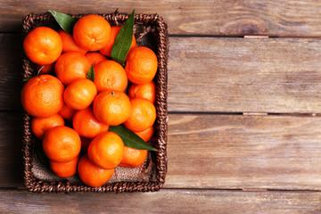 Fresh ripe mandarins in wooden box, on wooden background
