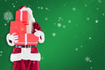 Composite image of santa covers his face with presents