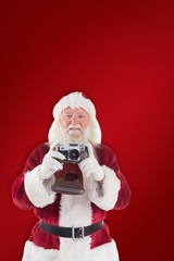 Composite image of santa is taking a picture