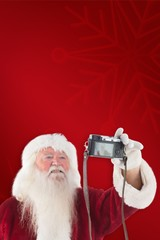 Composite image of santa claus makes a selfie