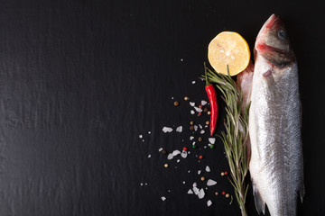 Fresh fish, lemon, pepper and rosemary on a black background. Ti