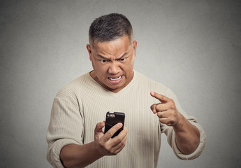 angry middle aged man while on mobile, pointing at smart phone
