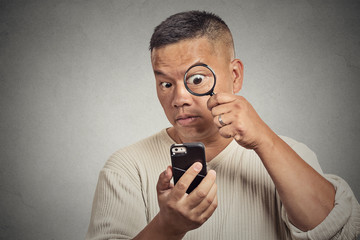 man looking through magnifying glass on smart phone