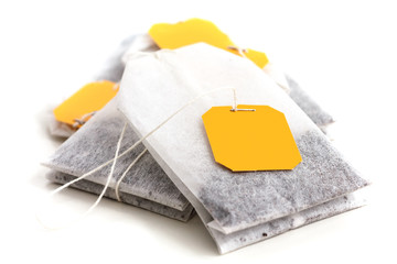 Tagged teabags with string on white surface.