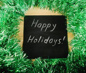 "on the black Board, white chalk written ""happy holidays"""