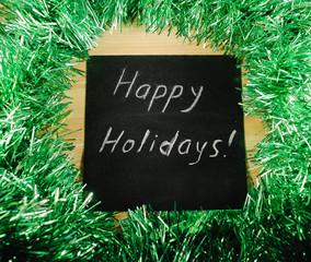 "on the black Board, white chalk written ""happy holidays"""