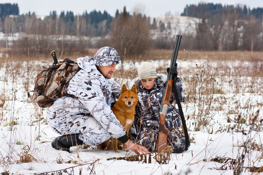 hunter shows his son traces of animals on the snowy field