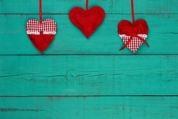 Red country hearts hanging on antique teal blue wood background