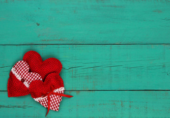 Red heart border on antique teal blue wooden background