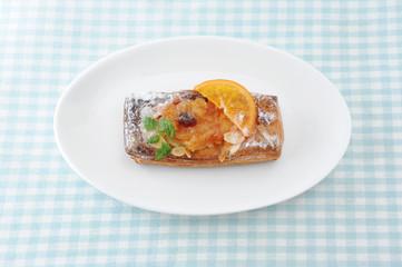 お皿にのせた オレンジ マーマレード パイのお菓子 テーブルクロス