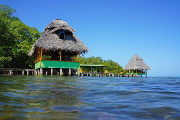 Tropical huts with thatched roof over the sea