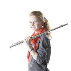 young blond girl sits and holds clarinet in studio