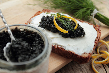 Black caviar and cream cheese on dark bread for appetizer