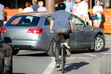 Fototapete - Man with helmet bicycling in traffic