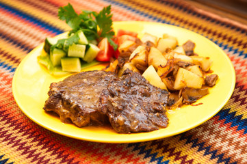 the roasted lamb with potatoes on the yellow plate