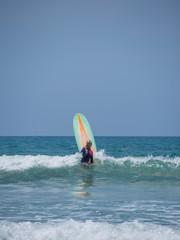 Beautiful young woman surfing in Kuta
