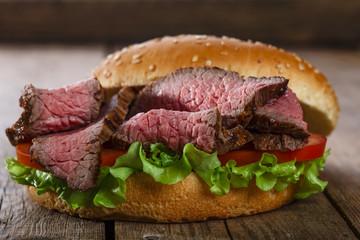 Fototapete - roast beef hamburger sandwich on a wooden surface