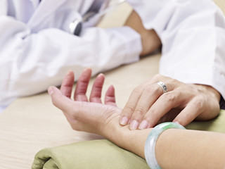 doctor taking pulse of a patient