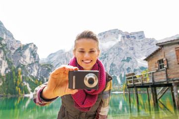 Smiling woman taking photo on lake braies in south tyrol, italy