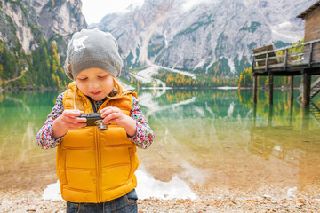 Child checking photos in camera on lake braies in south tyrol