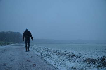 man walking in snowy meadow