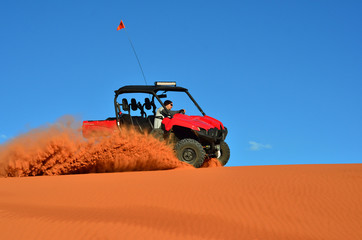 Man Driving a Four Wheeler on Sand with Blue Sky