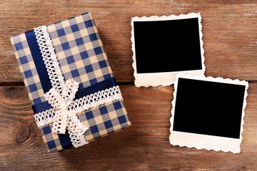 Blank photo frames and present box on wooden table background