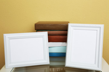 Photo frames with books on coffee table on wallpaper background
