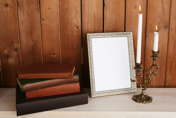Photo frame with candles and books
