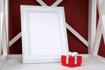 Photo frame with present box on shelf, on color wall background