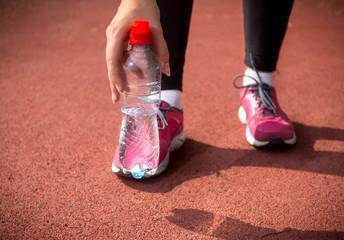 woman runner holding plastic bottle of water on running track