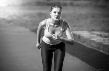 beautiful slim woman running on stadium at sunny day