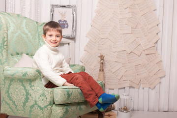 Little smiling boy on chair in Christmas interior