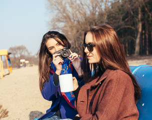 Two girls taking picture with an old camera