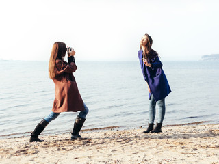 girl in a blue coat posing her girlfriend on the beach