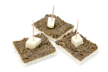 Canapes with olive paste on white background