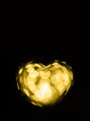 Sparkling golden bokeh heart on black background