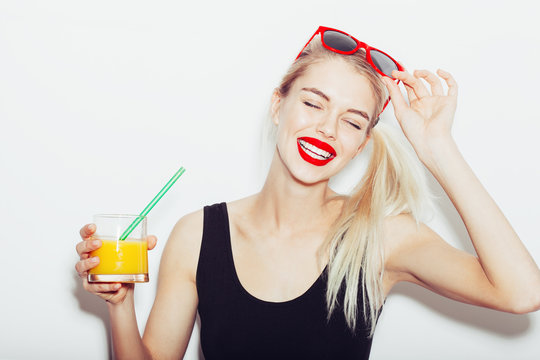Pretty smiling blonde woman in sunglasses with cocktail