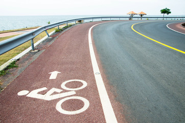 Bicycle route sign on the road by the sea