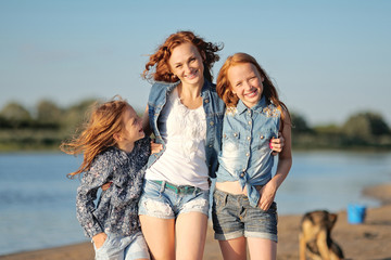 mother and her two daughters on the beach in summer