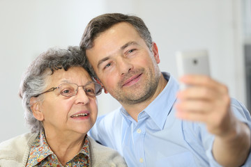 Elderly woman with son making selfy picture with smartphone
