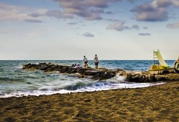 Persone sugli scogli con il mare mosso