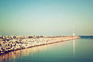 marina with the lighthouse and the sea. vintage filtered image